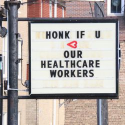"""The sign outside of Norwood Auto Service in Norwood Park reads """"honk if you love our healthcare workers,"""" Tuesday, April 7, 2020."""