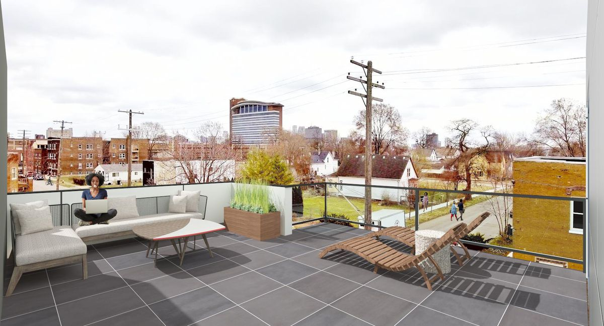 A resident works on a couch on a tiled deck overlooking North Corktown