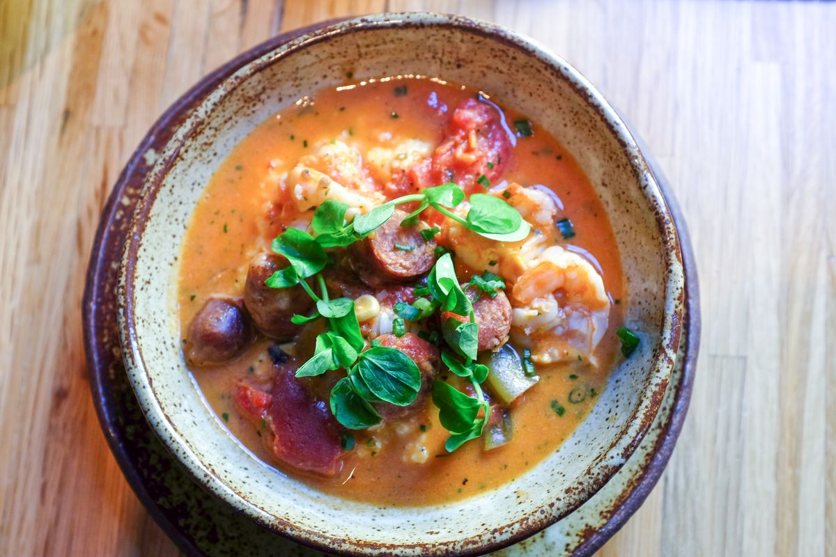 A bowl of shrimp and grits garnished with peppers