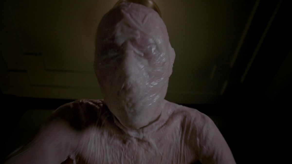 a pale, faceless slender figure