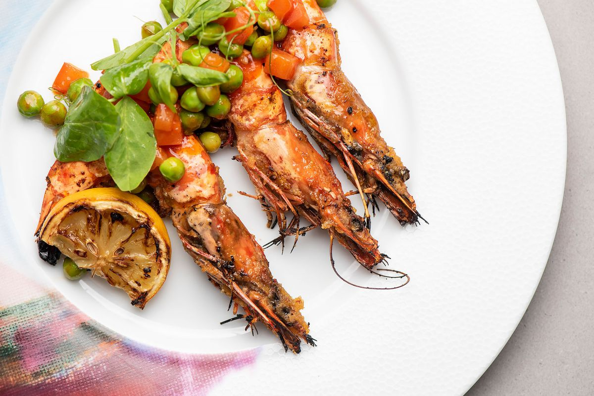 Jumbo prawns with peas and grilled lemon on a white plate.