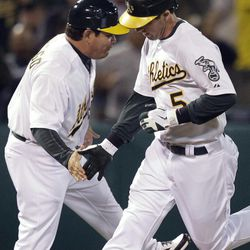 Oakland Athletics' Stephen Drew, right, is congratulated by third base coach Mike Gallego after hitting a home run off Seattle Mariners' Blake Bevan in the third inning of a baseball game Friday, Sept. 28, 2012, in Oakland, Calif.