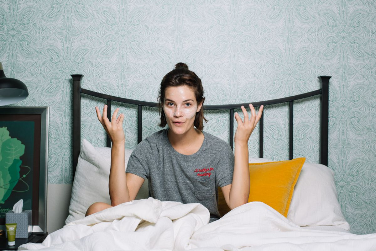 A woman in bed in a Richer Poorer x Origins collaboration T-shirt and a face mask.