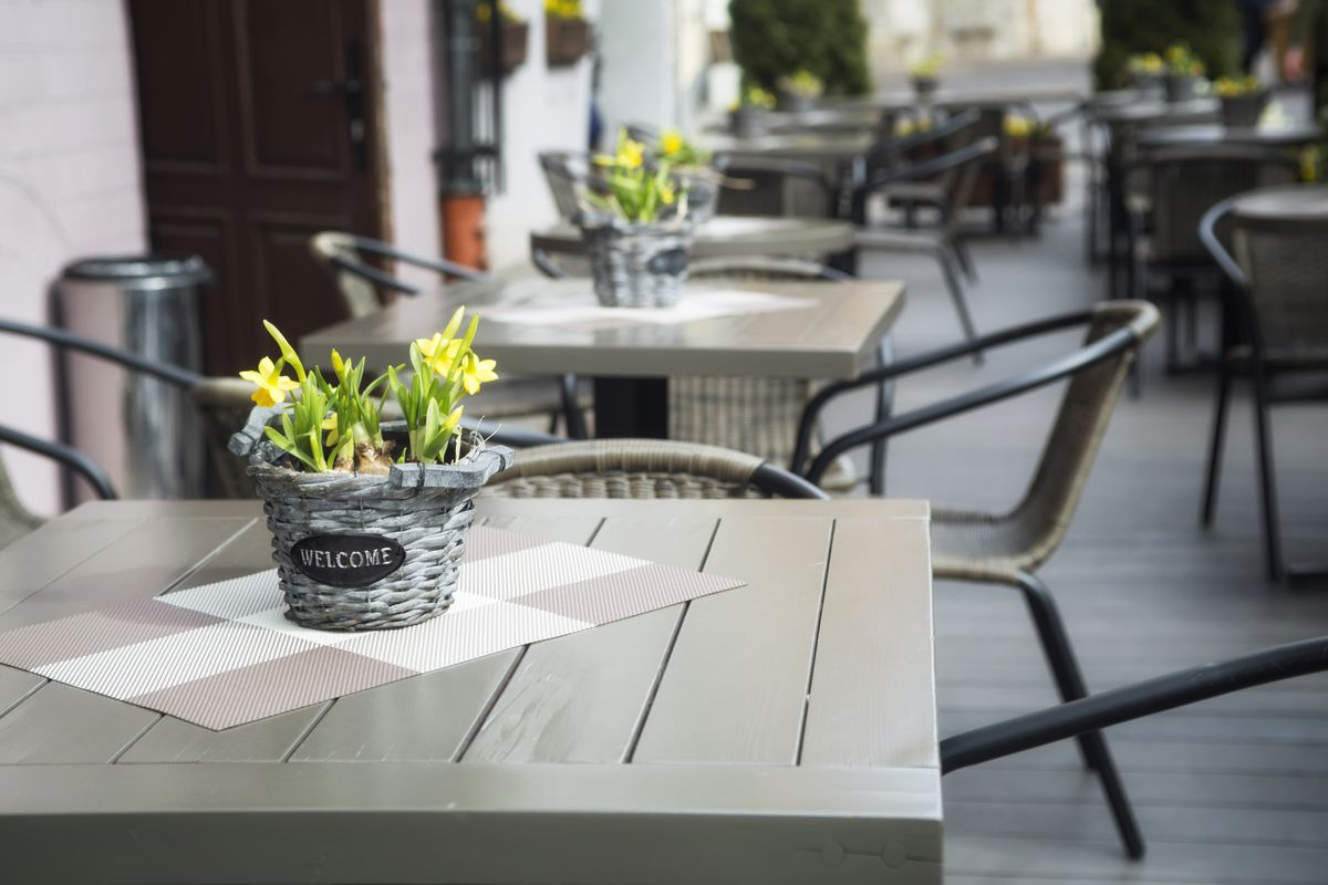 A grayish table on an outdoor patio with a green plant in the center and various chairs scattered around