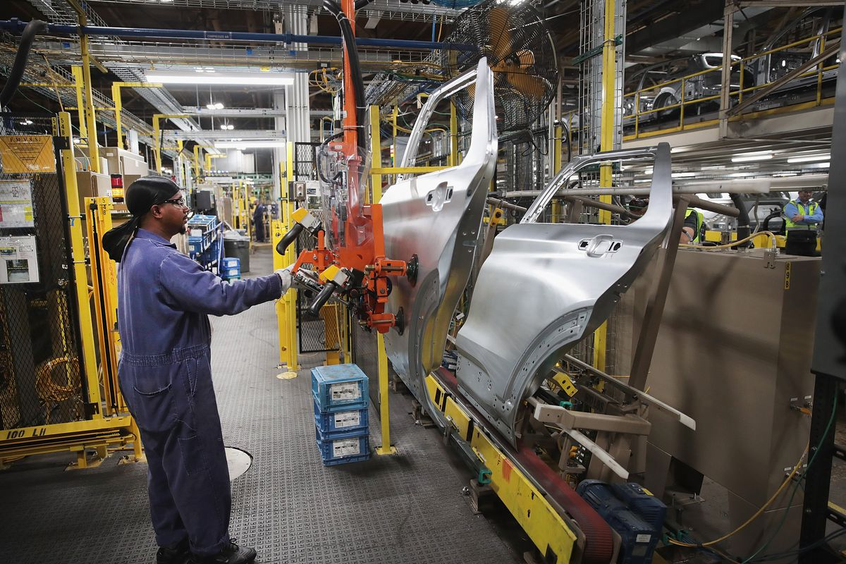 A jumpsuit man in a car manufacturing plant works on car doors suspended from a wall.