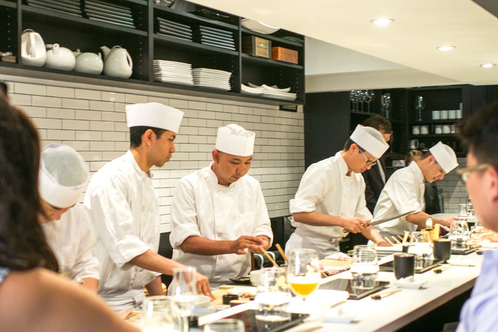 A series of people in white chef's outfits and hats work behind a counter, slicing sushi and preparing dishes for customers