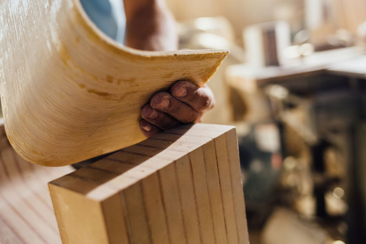 A piece of wood being bent by hand