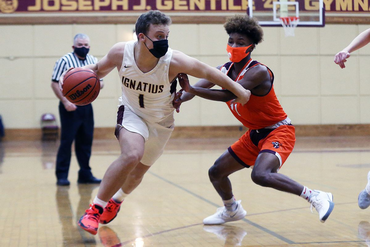 St. Ignatius' Parker Higginbottom (1) sweeps his arm to clear out Brother Rice's Ahmad Henderson (11).