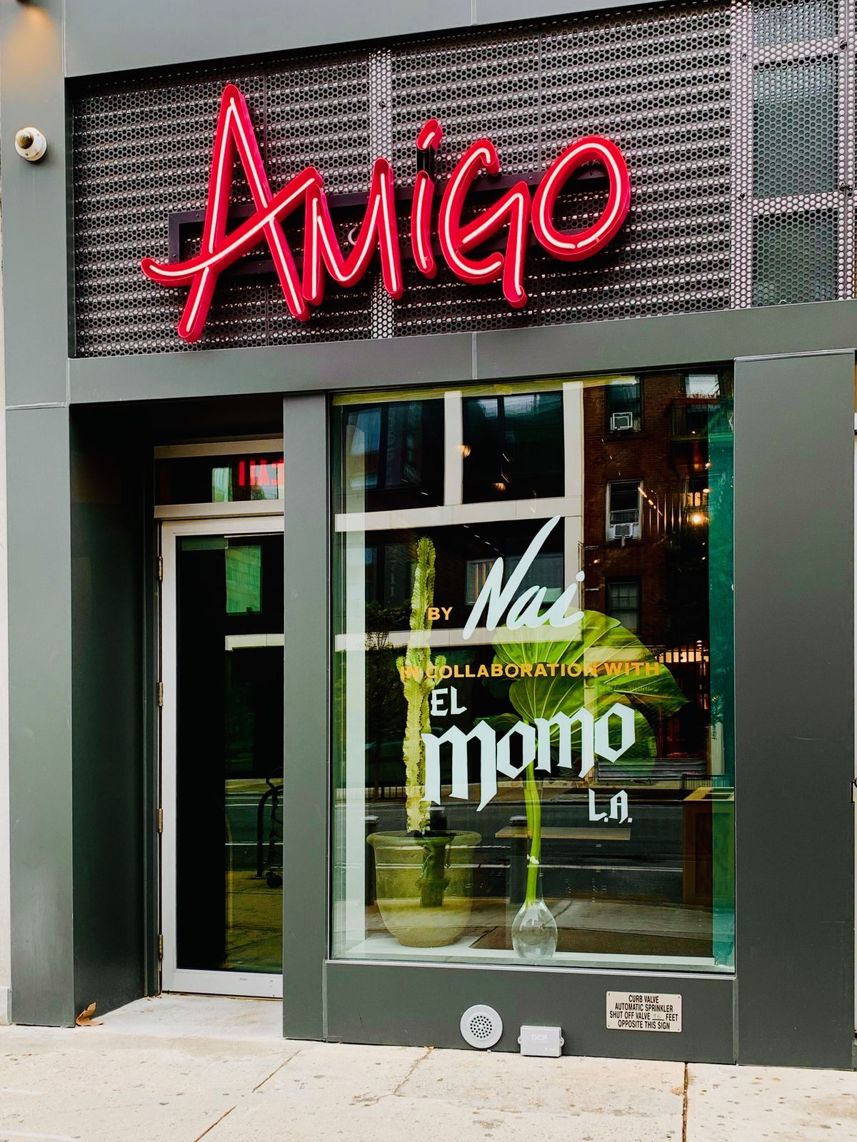 The dark exterior of the restaurant with Amigo in bright red letters above the doorway