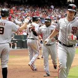 San Francisco Giants' Buster Posey, right, runs back to the dugout after celebrating his home run against the Arizona Diamondbacks as teammates Brandon Belt (9), Pablo Sandoval, and Aubrey Huff (17) continue the high-fives during the third inning in an MLB baseball game Sunday, April 8, 2012, in Phoenix.