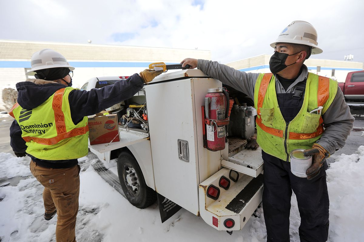 Dominion Energy utility workers Kylie Hrubes, left, and Ramone Barrera put tools away in their truck as they replace a gas meter in West Valley City on Wednesday, Feb. 17, 2021.