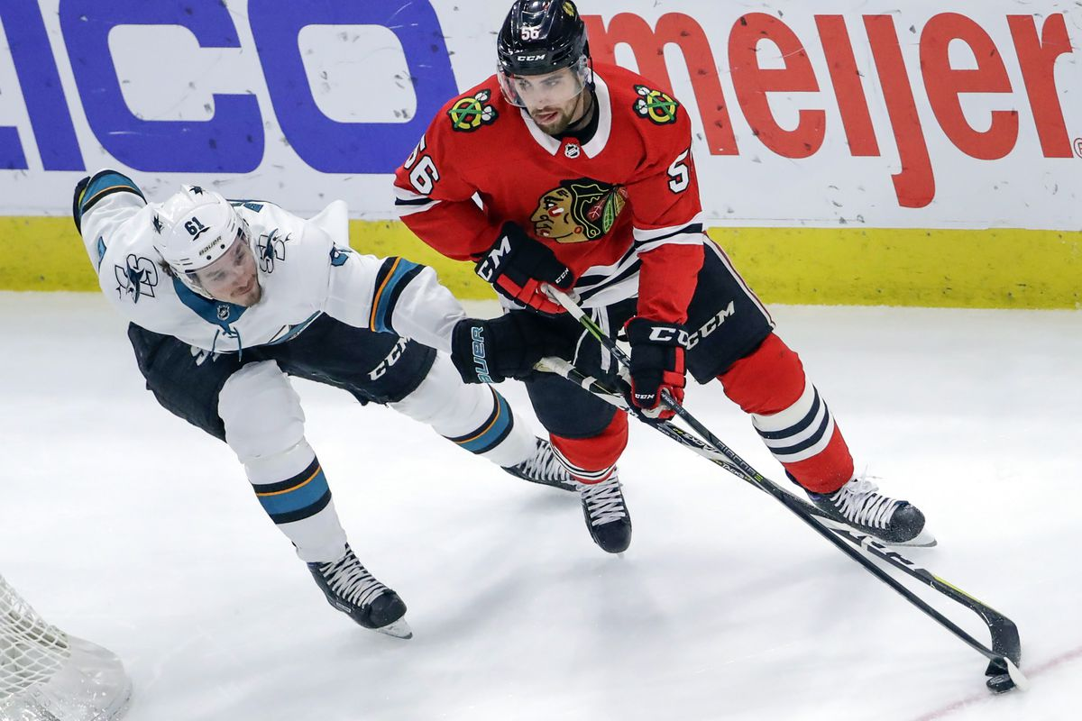Feb 23, 2018; Chicago, IL, USA; San Jose Sharks defenseman Justin Braun (61) battles for the puck with Chicago Blackhawks defenseman Erik Gustafsson (56) during the second period at United Center.