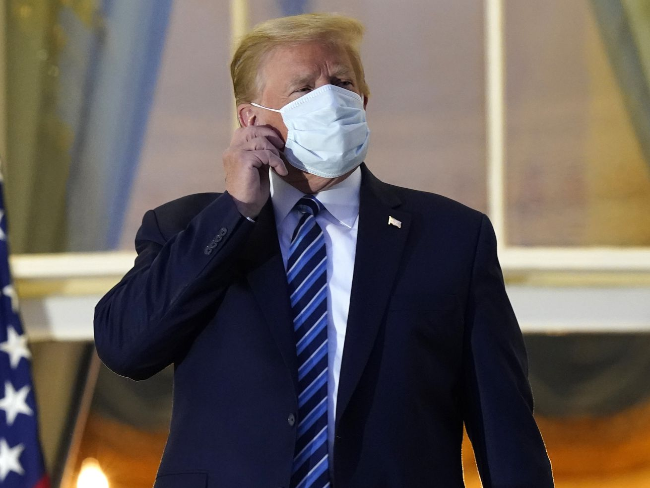 President Donald Trump removes his mask as he stands on the balcony outside of the Blue Room as he returns to the White House Monday, Oct. 5, 2020, in Washington, after leaving Walter Reed National Military Medical Center, in Bethesda, Md. Trump announced he tested positive for COVID-19 on Oct. 2.