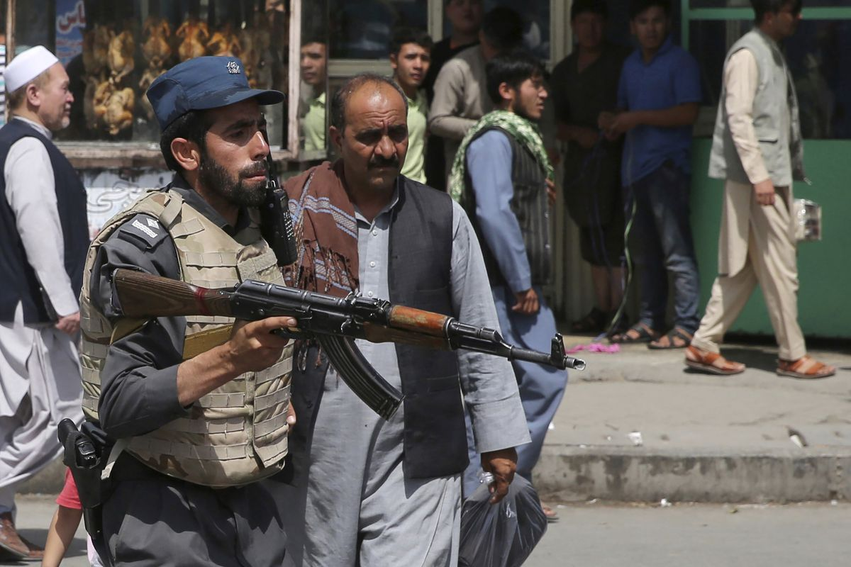 An Afghan policeman stands guard after an explosion near the police headquarters in Kabul, Afghanistan, Wednesday, Aug. 7, 2019. A suicide car bomber targeted the police headquarters in a minority Shiite neighborhood in western Kabul on Wednesday, setting