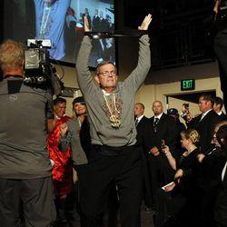 Former Utah Gov. Mike Leavitt walks ahead of former Massachusetts Gov. Mitt Romney as his ring man during the Charity Vision Fight Night event in Salt Lake City, Friday, May 15, 2015.