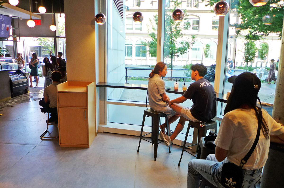 Three bubble tea patrons sit on stools and look out a big window...