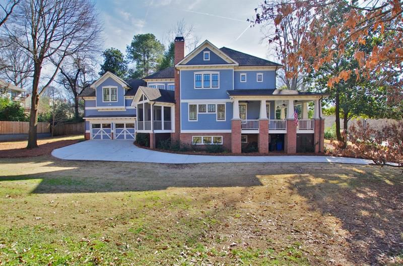 A large blue home with several porches and a two-car garage.