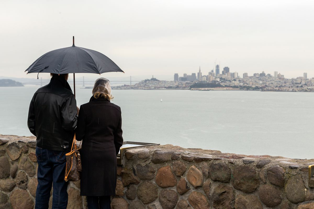 Tourists with umbrellas take a glimpse of San Francisco in the rain from the viewpoint at the Lone Sailors Memorial.