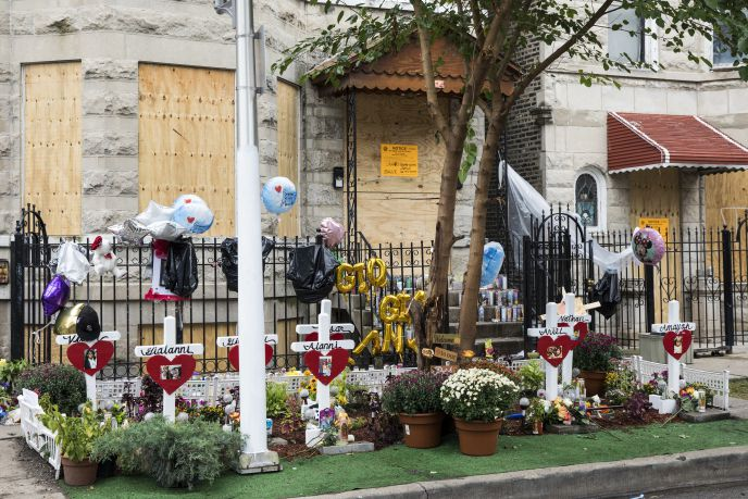 A memorial remains in front of a three-story apartment building in the 2200 block of South Sacramento Avenue on Wednesday. A fire in a second-story apartment behind this building claimed the lives of 10 children. Eight died Sunday, another on Monday and t