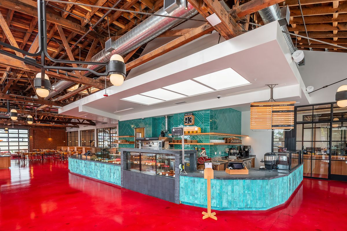 A teal counter and red floor of a new coffee shop.