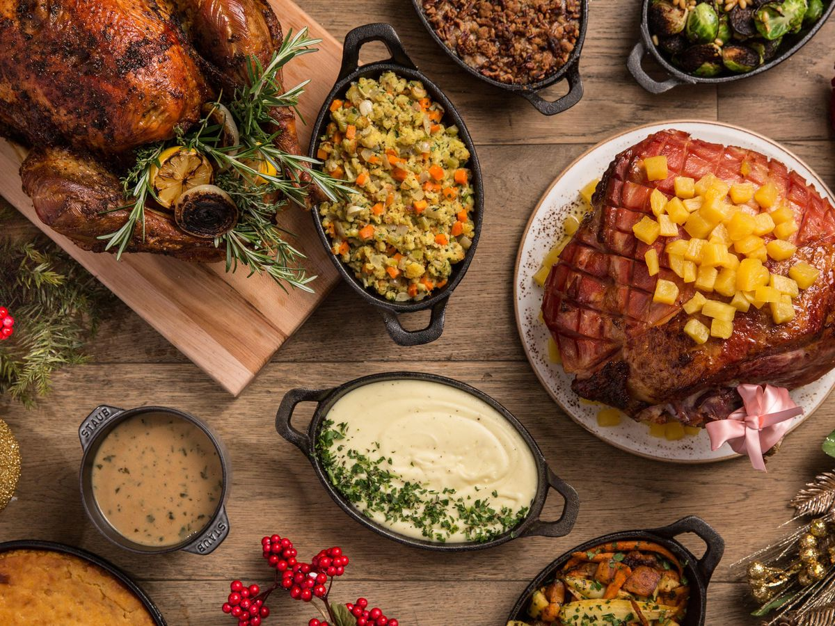 A spiral ham, a whole turkey, and a variety of sides spread out on a table.