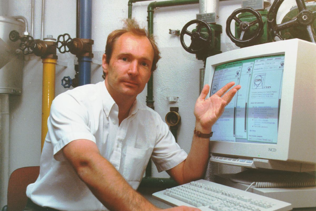 Tim Berners-Lee is sitting at a table, looking at the camera and gesturing to the computer monitor in front of him.