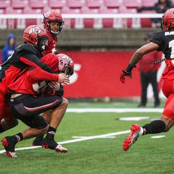 Defensive back Corrion Ballard, right, runs while defensive back Tyrone Smith tackles wide receiver Samson Nacue at Rice-Eccles Stadium in Salt Lake City on Saturday, March 25, 2017.