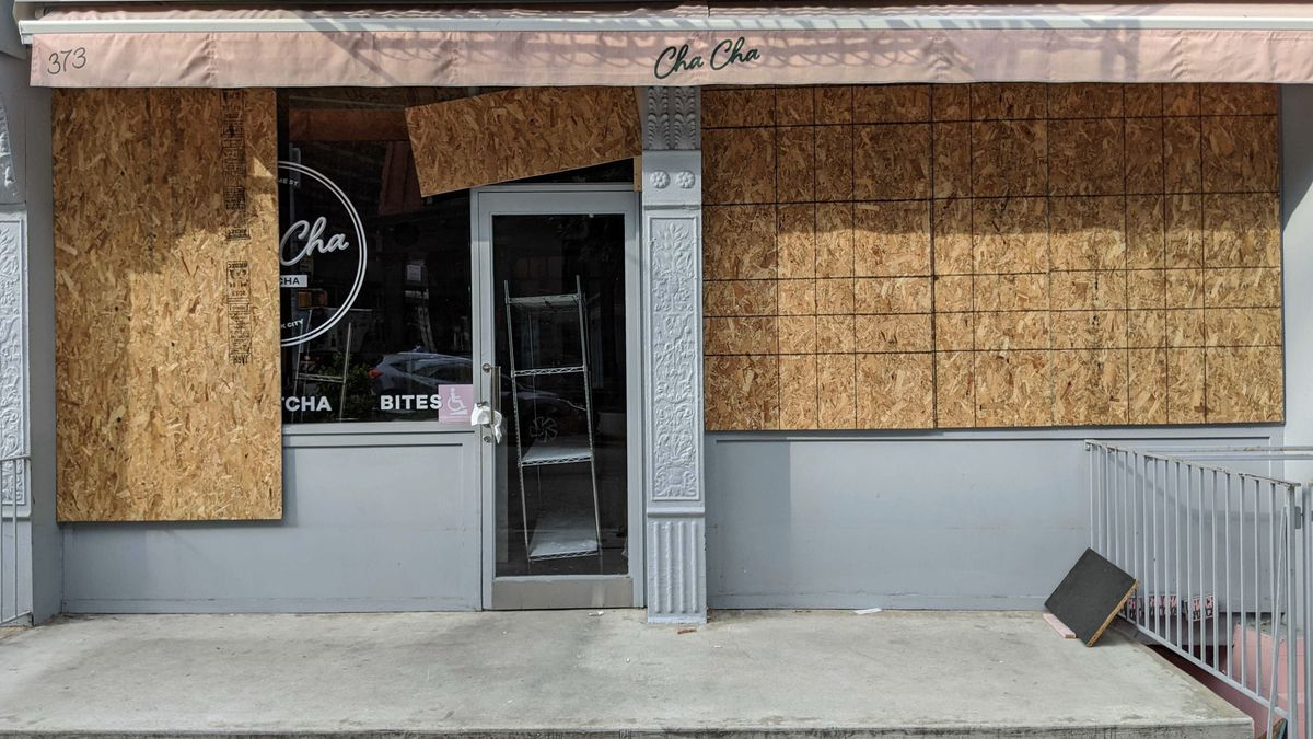 """The storefront of a cafe is partially boarded up with plywood. A light pink awning has the words """"Cha Cha"""" in green font"""