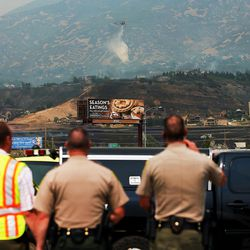 Law enforcement watch as a chopper drops water on a fire b urning near Weber Canyon on Tuesday, Sept. 5, 2017.