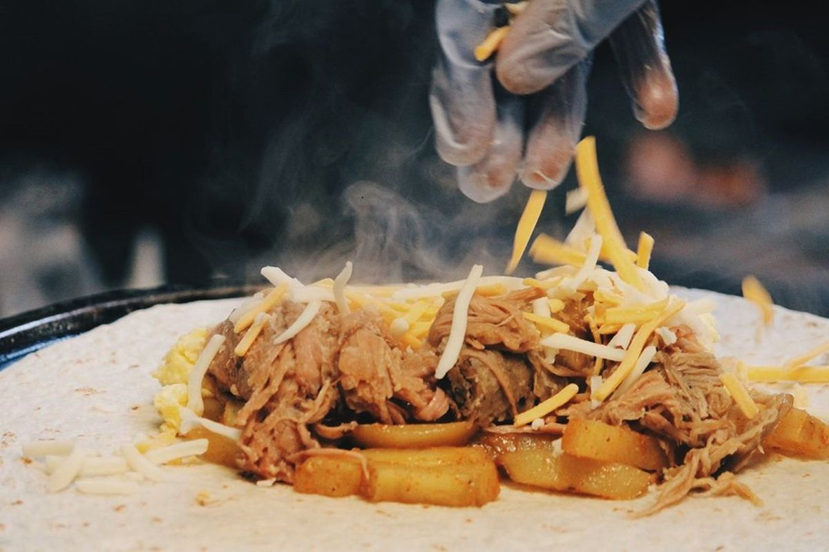 Chun's bomber at Kono's Northshore, created with roasted Kalua pork, eggs, potatoes, and shredded cheddar jack cheese.