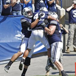 Brigham Young Cougars running back Michael Alisa (42) is congratulated by team mates  after scoring a touchdown during the first half as Brigham Young University plays Weber State University in football  Saturday, Sept. 8, 2012, in Provo, Utah.