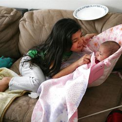 Ariza Carreon, 7, plays with her baby sister Adriana at home in Taylorsville on Saturday, Feb. 9, 2013. Carreron's family was recently evicted, but they managed to land on their feet.
