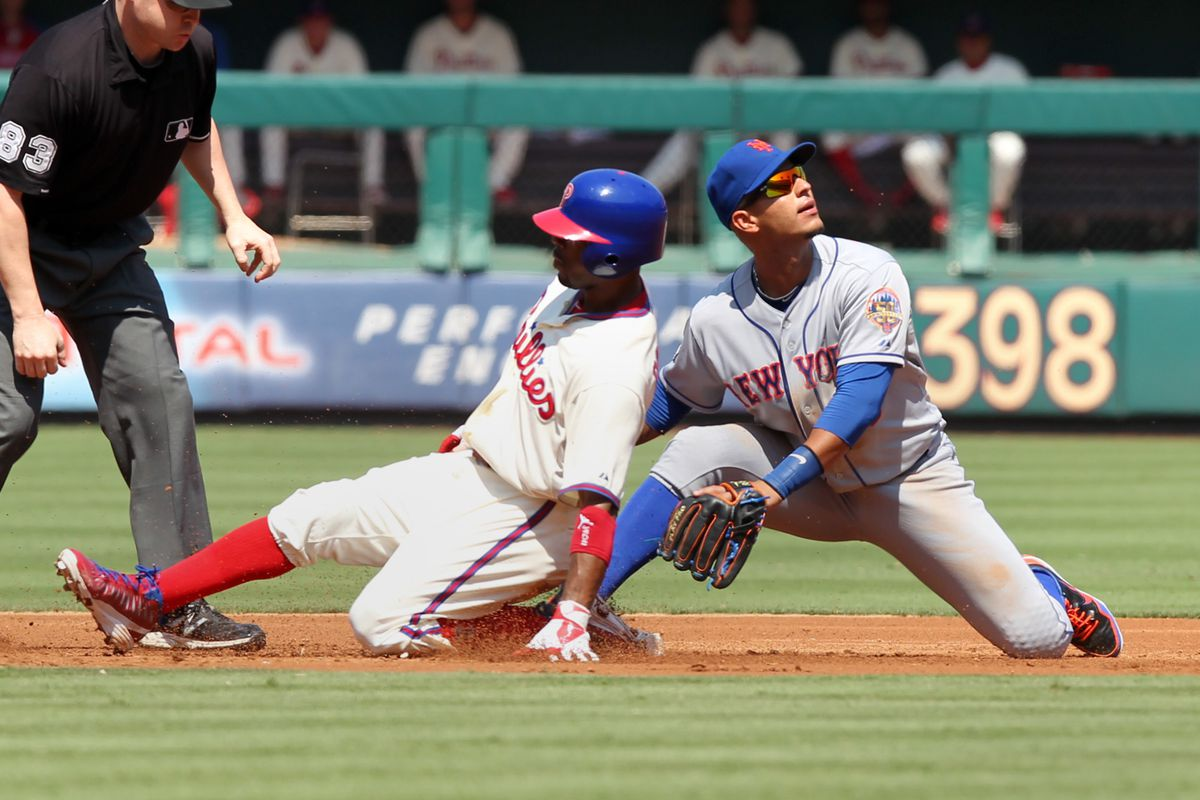 PHILADELPHIA - AUGUST 30: Jimmy Rollins #11 of the Philadelphia Phillies slides into second base as Charlie Manuel waits to berate him in the dugout and the jet from LA waits patiently to come get him. (Photo by Hunter Martin/Getty Images)