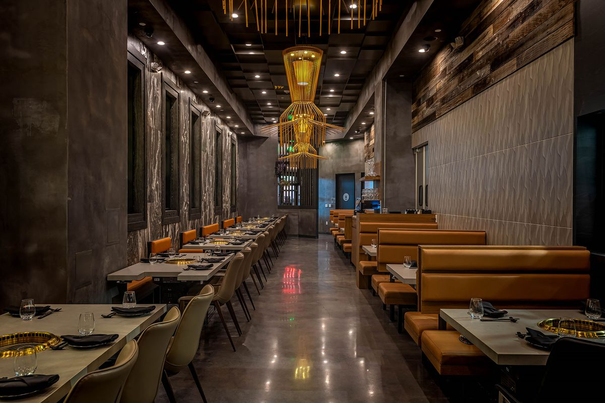 Wide view of ABSteak dining room with tan booths and lineup of tables with chairs.