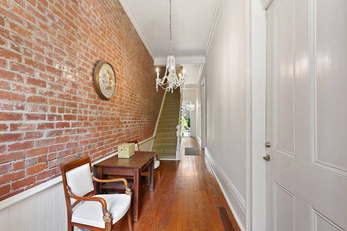 A brick foyer with a staircase, crystal chandelier, and doors leading outdoors.