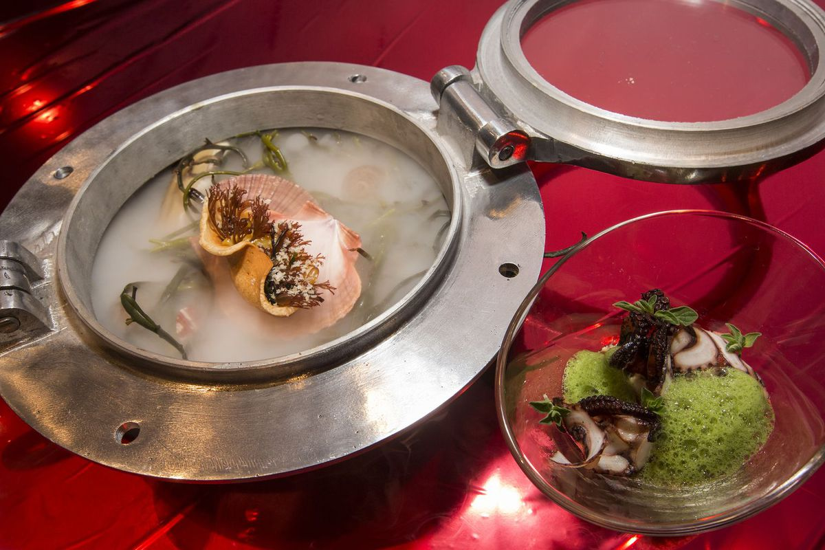A metallic portal-shaped bowl holds a scallop dish with dry ice beside a glass bowl of octopus and green foam.