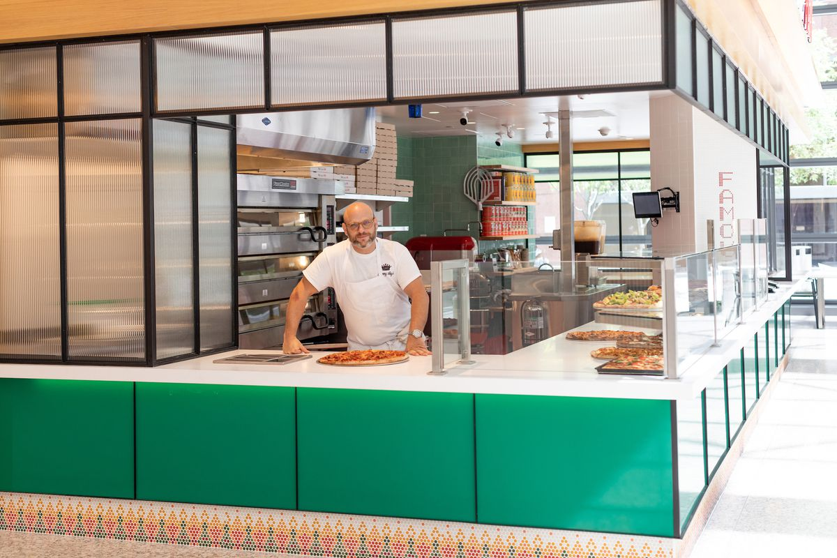 A chef in a white shirt leans on the counter of his new pizza restaurant.