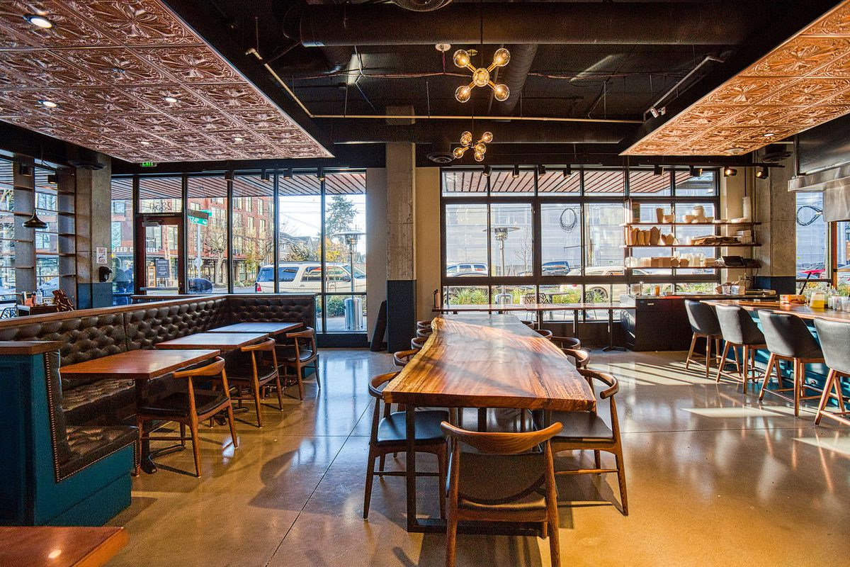 The interior of Communion on a sunny day facing the windows, and a communal table in the center