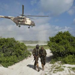 FILE - In this Wednesday, Dec. 14, 2011 file photo, two Kenyan army soldiers shield themselves from the downdraft of a Kenyan air force helicopter as it flies away from their base near the seaside town of Bur Garbo, Somalia. Kenya's military said Friday, Sept. 28, 2012 that its troops attacked Kismayo, the last remaining port city held by al-Qaida-linked al-Shabab insurgents in Somalia, during an overnight attack involving a beach landing.