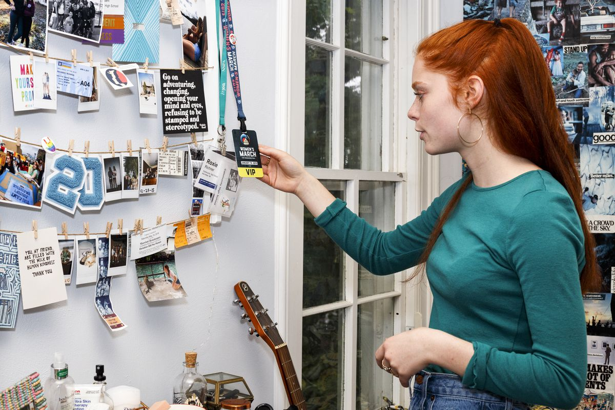 Roxie Richner, 17, holds her Women's March VIP pass hanging from her wall in her bedroom.