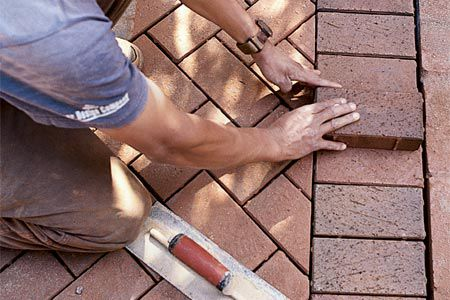 Person laying a brick to build a walkway.