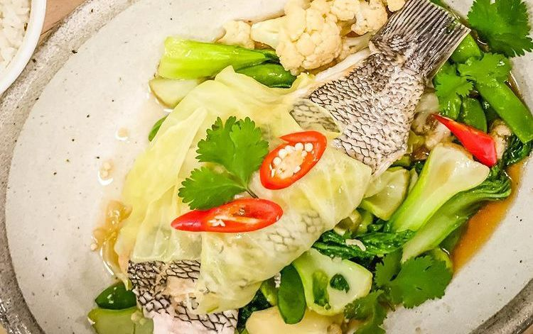 A fish with tail but no head sprinkled with sliced red chiles and surrounded by other vegetables.