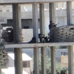In this citizen journalism image provided by the Local Coordination Committees in Syria and accessed on Tuesday, April 17, 2012, A Syrian government solider stands near a machine gun inside a building in Daraa, Syria. Activists say Syrian government forces are pounding a rebel stronghold with mortar fire, violating a week-old cease-fire the international community is reluctant to declare dead despite ongoing violence. (AP Photo/Local Coordination Committees in Syria) THE ASSOCIATED PRESS IS UNABLE TO INDEPENDENTLY VERIFY THE AUTHENTICITY, CONTENT, LOCATION OR DATE OF THIS HANDOUT PHOTO