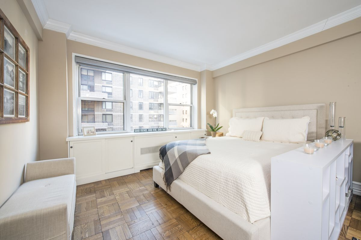 A bedroom with a large bed, beige walls, and hardwood floors.