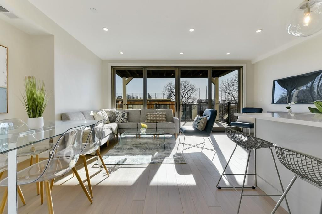An open living room-dining room area leading to a private deck.