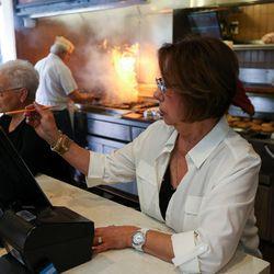 Rula Katzourakis serves customers while her husband, John, tends to the broiler at Crown Burgers in Salt Lake City on Friday, Aug. 5, 2016. John and Rula Katzourakis have owned and operated Crown Burgers for 38 years.
