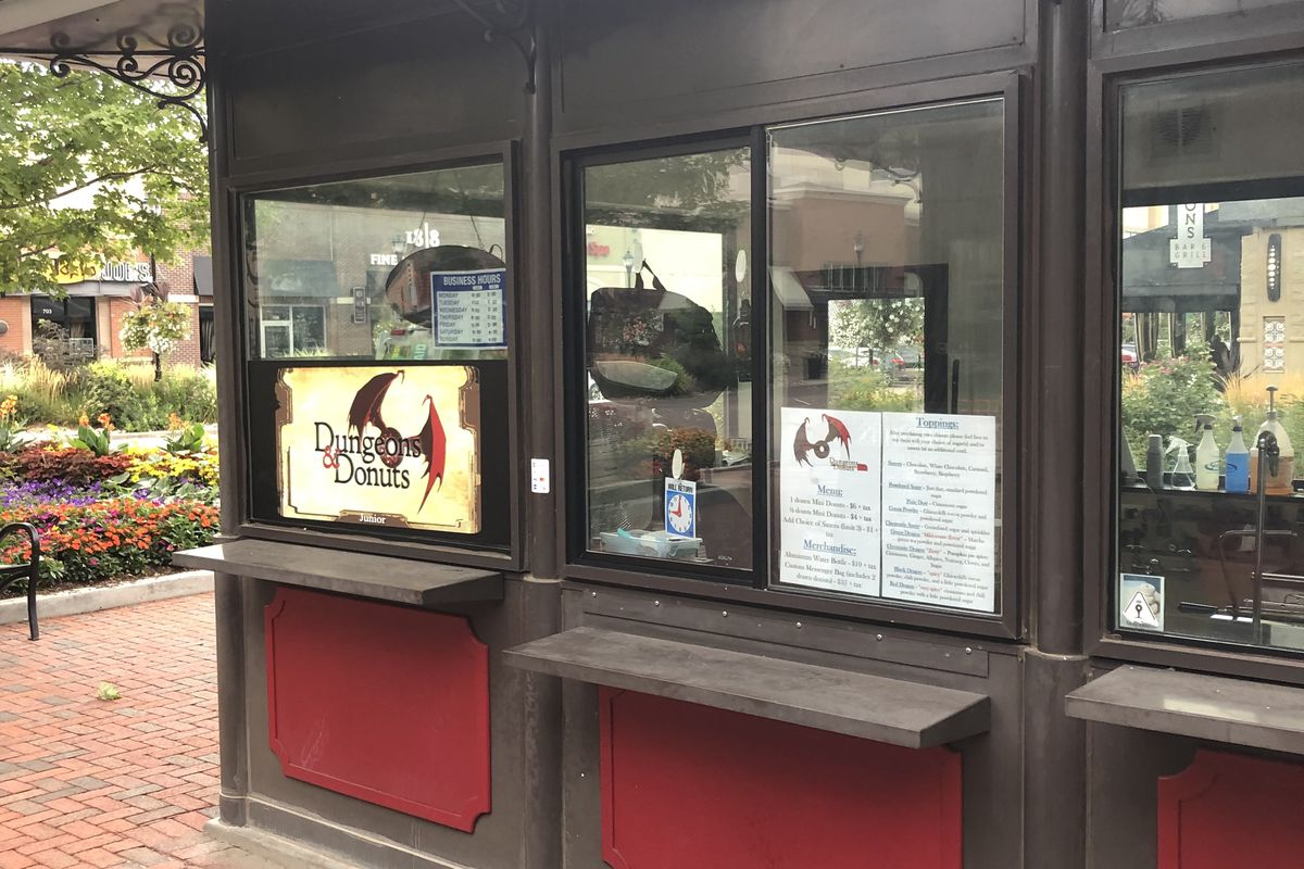 A side view photo of the red and brown Dungeons & Donuts kiosk in Centennial with the menu and signage visible