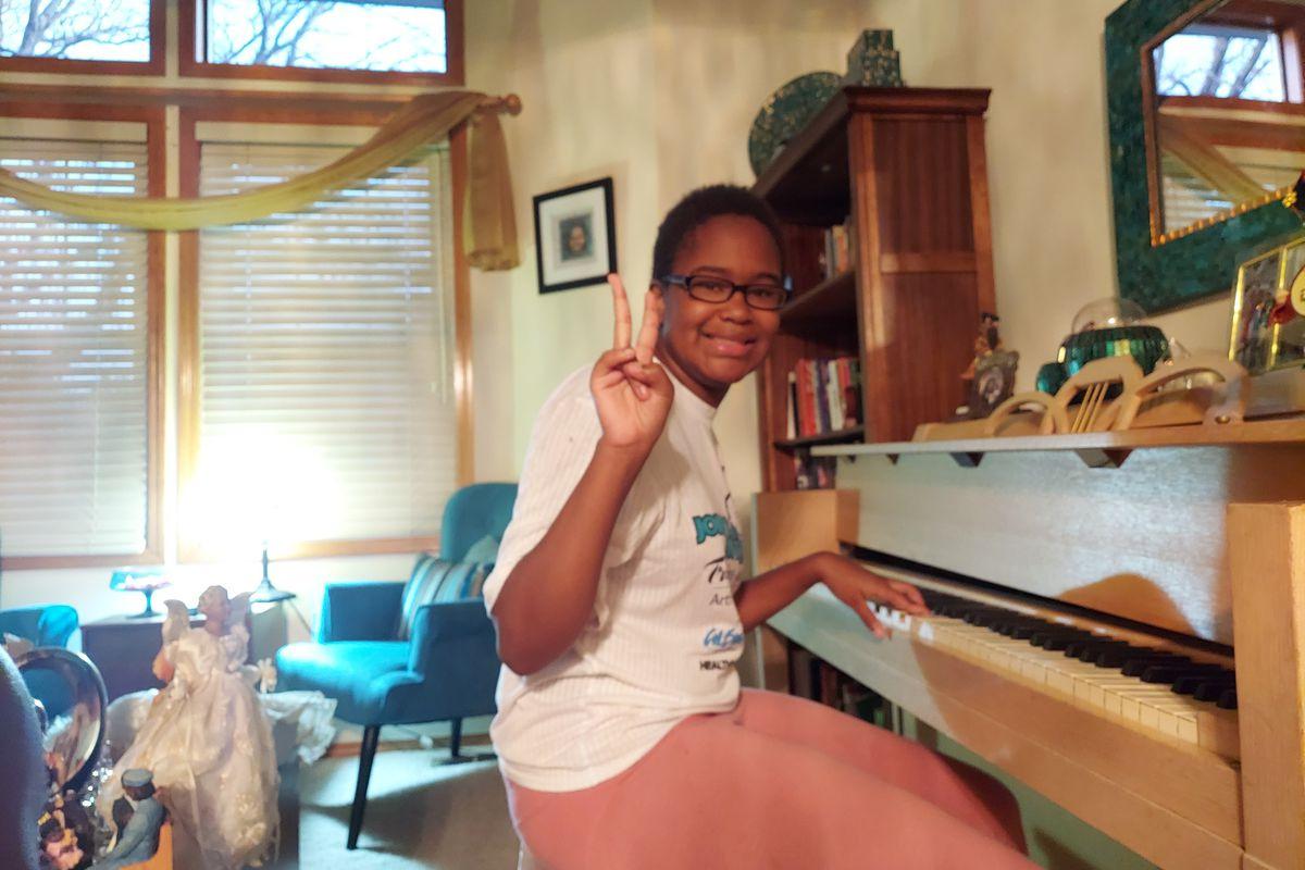 Karinne Jones, 14, sits at a piano and holds up a peace sign at the camera while smiling.