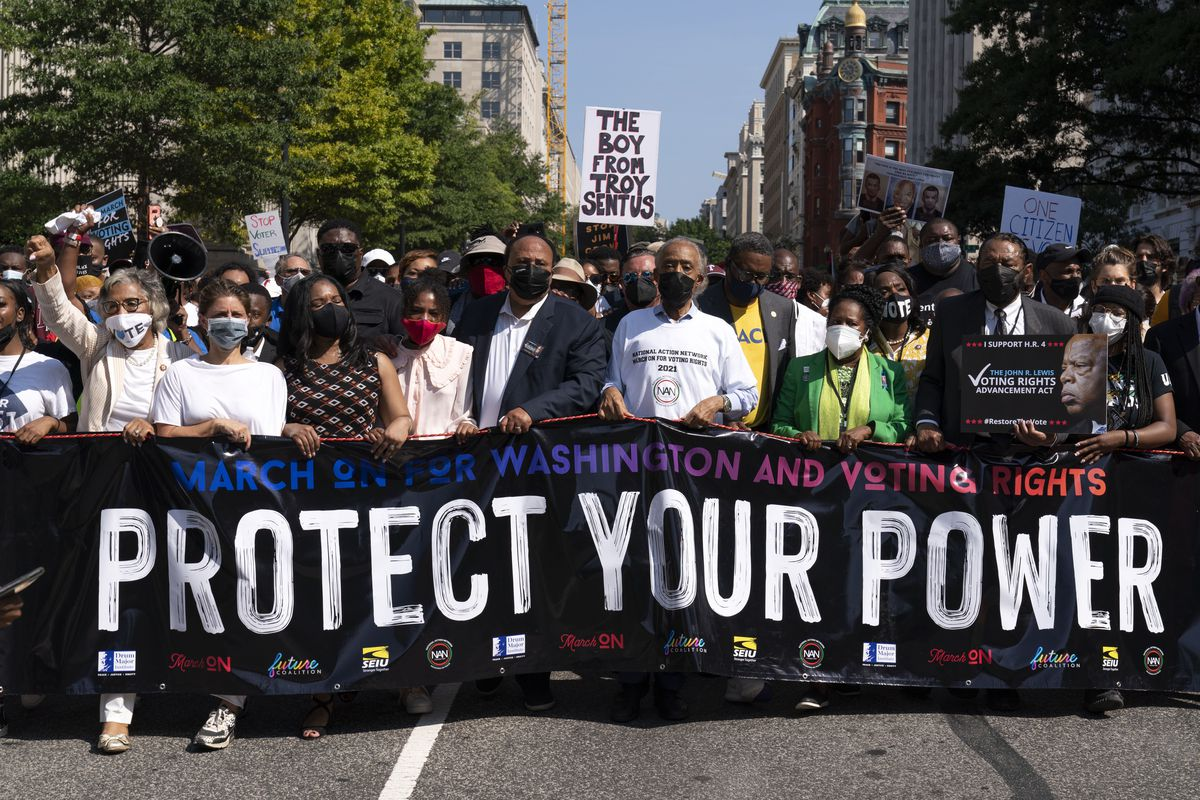 The Rev. Al Sharpton, third from right in front, holds a banner with Martin Luther King, III, Rep. Sheila Jackson Lee, D-Texas, second from right, and Rep. Al Green, D-Texas, right, among others, during the march to call for sweeping protections against a further erosion of the Voting Rights Act of 1965, Saturday in Washington.