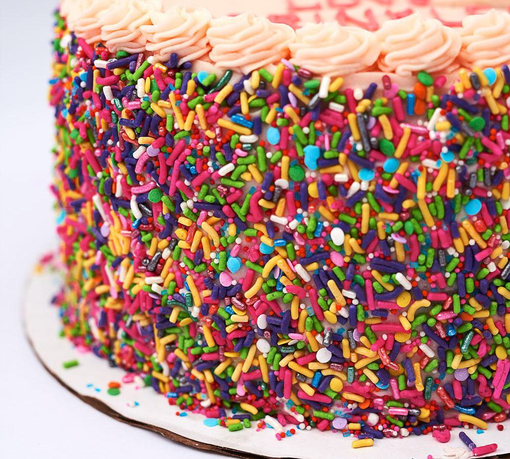 The side of a frosted cake is decorated with rainbow sprinkles